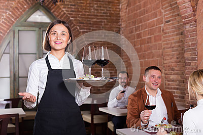 Nice female waiter showing country restaurant