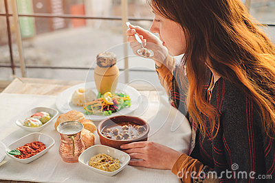 Woman eat turkish food from meatball and pottery kebab