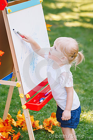 Child kid girl standing outside in summer autumn park drawing on easel with markers looking away playing studying