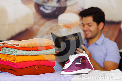 A pile of clothes next to the iron with gorgeous man smiling behind while he is reading a book