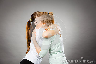 Two happy friends women hugging