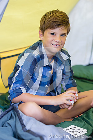 Smiling boy playing cards while sitting in tent