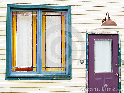 Purple door and green window in need of repaint in weatherboard