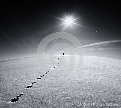 Man.Earth.Universe.Lonely man walking on snow crust field on the trail of a hare on the background of the sun and the flying plane