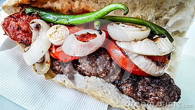 Turkish Kofte Ekmek / Meatball Sandwich with tomatoes, onion and green pepper.