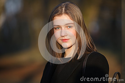 Close up emotional portrait of young happy beautiful woman with a slightly smile wearing black coat posing at evening golden hour