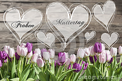 Happy mother`s day german text heart with pink and white tulips rustic wooden background greeting card spring flowers