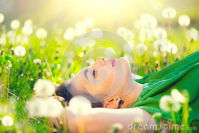 Young woman lying on the field in green grass and dandelions