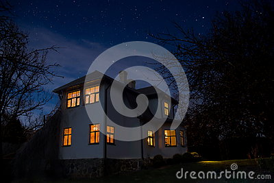 Romantic house with a light in the window. Night landscape in summer