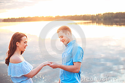 Marriage proposal on sunset . young man makes a proposal of betrothal to his girlfriend on the beach