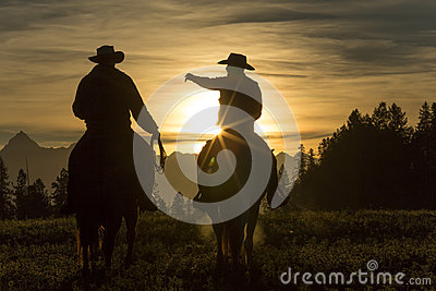 Cowboys riding across grassland early moring, British Colombia,