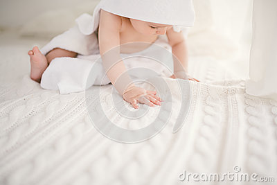 Beautiful smiling newborn baby boy covered with white bamboo towel with fun ears. Sitting on a white knit, wool plaid bright inter