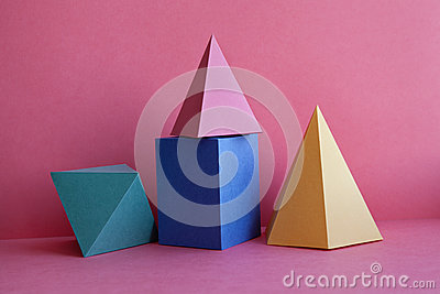 Platonic solids abstract geometric still life composition. Prism pyramid rectangular cube figures on pink paper