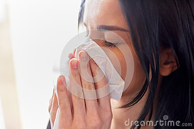Close up of woman with wipe blowing nose or crying