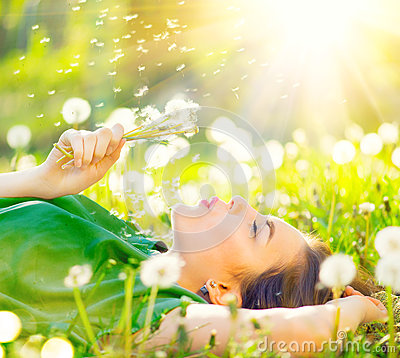 Beautiful woman lying on the field in green grass and blowing dandelion