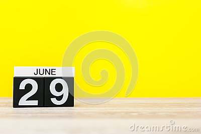June 29th. Day 29 of month, calendar on yellow background. Summer day. Empty space for text
