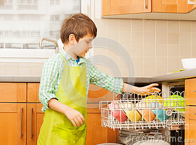 Kid boy getting out clean crockery of dishwasher