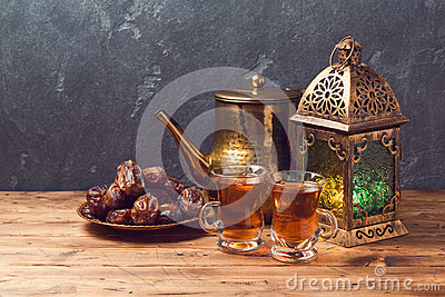 Lightened lantern, tea cups and dates on wooden table over blackboard background. Ramadan kareem holiday celebration