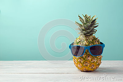 Pineapple with sunglasses on wooden table over mint background. Tropical summer vacation and beach party