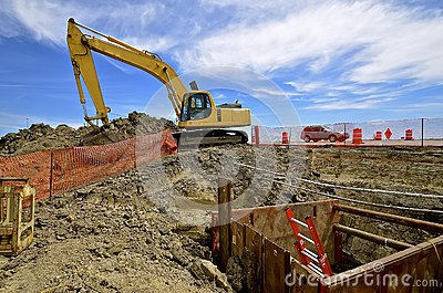 Road construction site with excavating machine