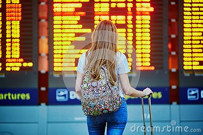 Tourist girl with backpack and carry on luggage in international airport, near flight information board
