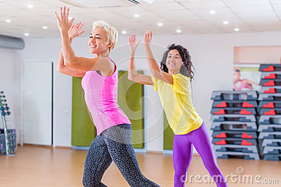 Happy female athletes doing aerobics exercises or Zumba dance workout to lose weight during group classes in fitness