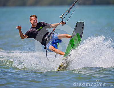 Clearwater, FL- March 12- Happy kite surfer swings his body in the air doing tricks on March 12, 2016