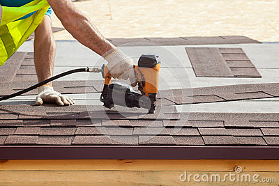 Construction worker putting the asphalt roofing shingles with nail gun on a new frame house.
