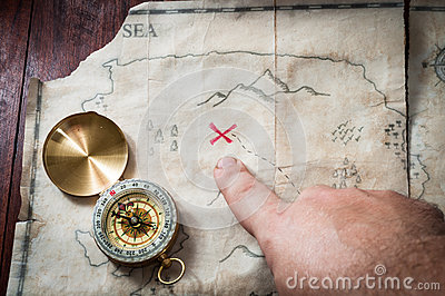 Man point with finger into red cross on Ancient Treasure map with compass on wooden desk