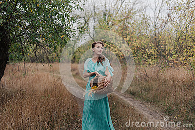 Romantic woman wearing long elegant dress standing on the field, autumn season, relaxation in countryside, enjoying nature, pleasu