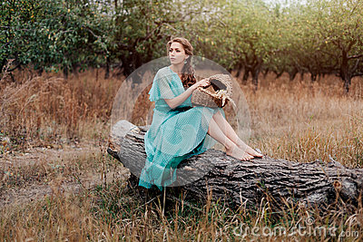 Romantic woman wearing long elegant dress sitting on the field, autumn season, relaxation in countryside, enjoying nature, pleasur