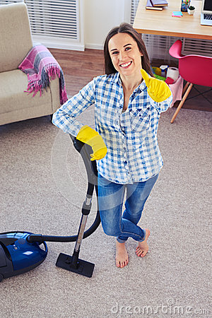Charming girl holding vacuum cleaner and showing clearness of ca