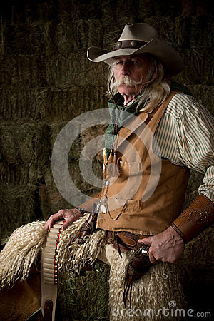 Authentic western cowboy with leather vest, cowboy hat and scarf portrait