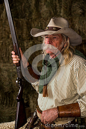 Authentic old west cowboy with shotgun, hat and bandanna in stable portrait