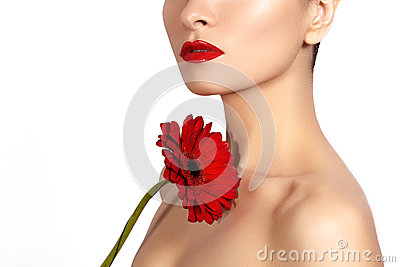 Close-up beauty photo sexy woman with red lips, lipstick and beautiful red flower. Spa clean skin
