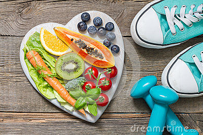 Healthy diet and sport concept with dumbbells trainers and food