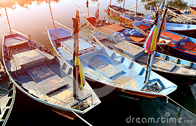 Row of small wooden fishing boats.