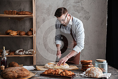 Concentrated young man baker cut the bread.