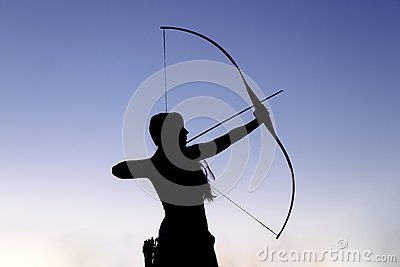 Female ginger hair archer shooting targets with her bow and arrow. Concentration, target, success concept.