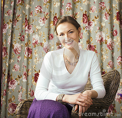 Pretty mature woman happy smiling sitting in room interior, life