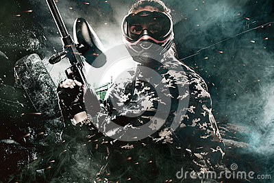 Heavily armed masked paintball soldier on post apocalyptic background. Ad concept.
