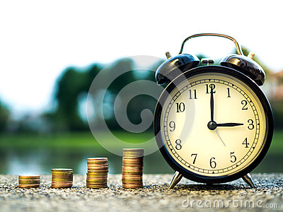 Close up of time and stack money coins, time value of money concept in business finance theme. Saving money for future