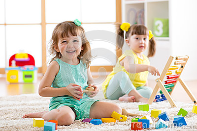 Children toddler and preschooler girls play logical toy learning shapes, arithmetic and colors in kindergarten or