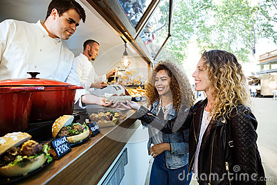 Two beautiful young women buying meatballs on a food truck.