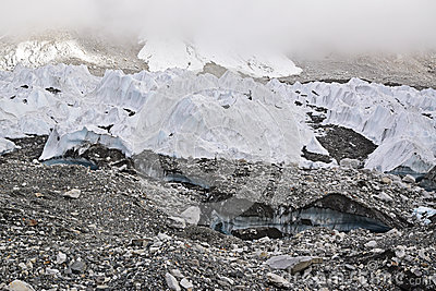 Melting ice glaciers due to global warming with thick mist at the top