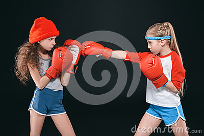 Side view of sportive girls pretending boxing isolated on black