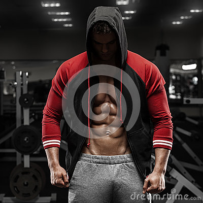 Muscular man with open jacket revealing abs in gym, workout. Shaped abdominal