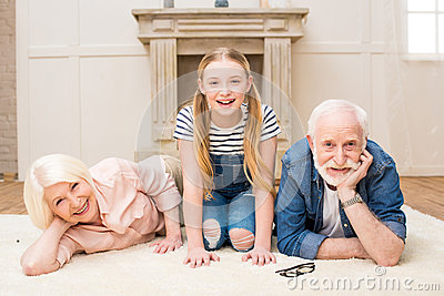Little girl with smiling grandpa and grandma resting together at home