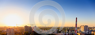 Aerial panoramic view of evening sunset cityscape, industrial area
