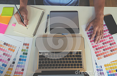 stock image of graphic design and color swatches and pens on a desk.